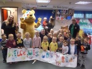 Children at Mama Bear's Soundwell with their welcome banner a